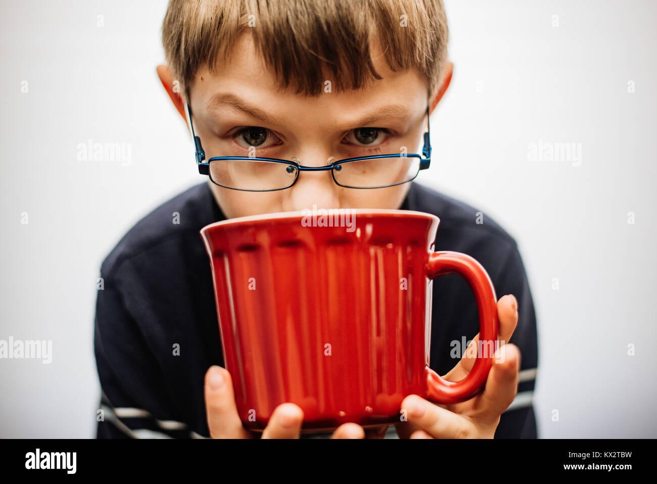 Un muchacho de 11 años con gafas mirando por encima del borde de una taza de té rojo. Imagen De Stock