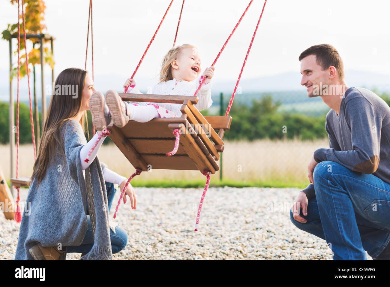 Familia Con Nina Balanceandose En Un Patio De Juegos La Infancia