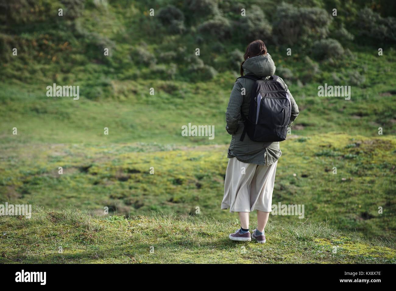 6a496f587400 ... caucásica de pie sobre una colina de hierba por ella misma con una  mochila y una falda larga