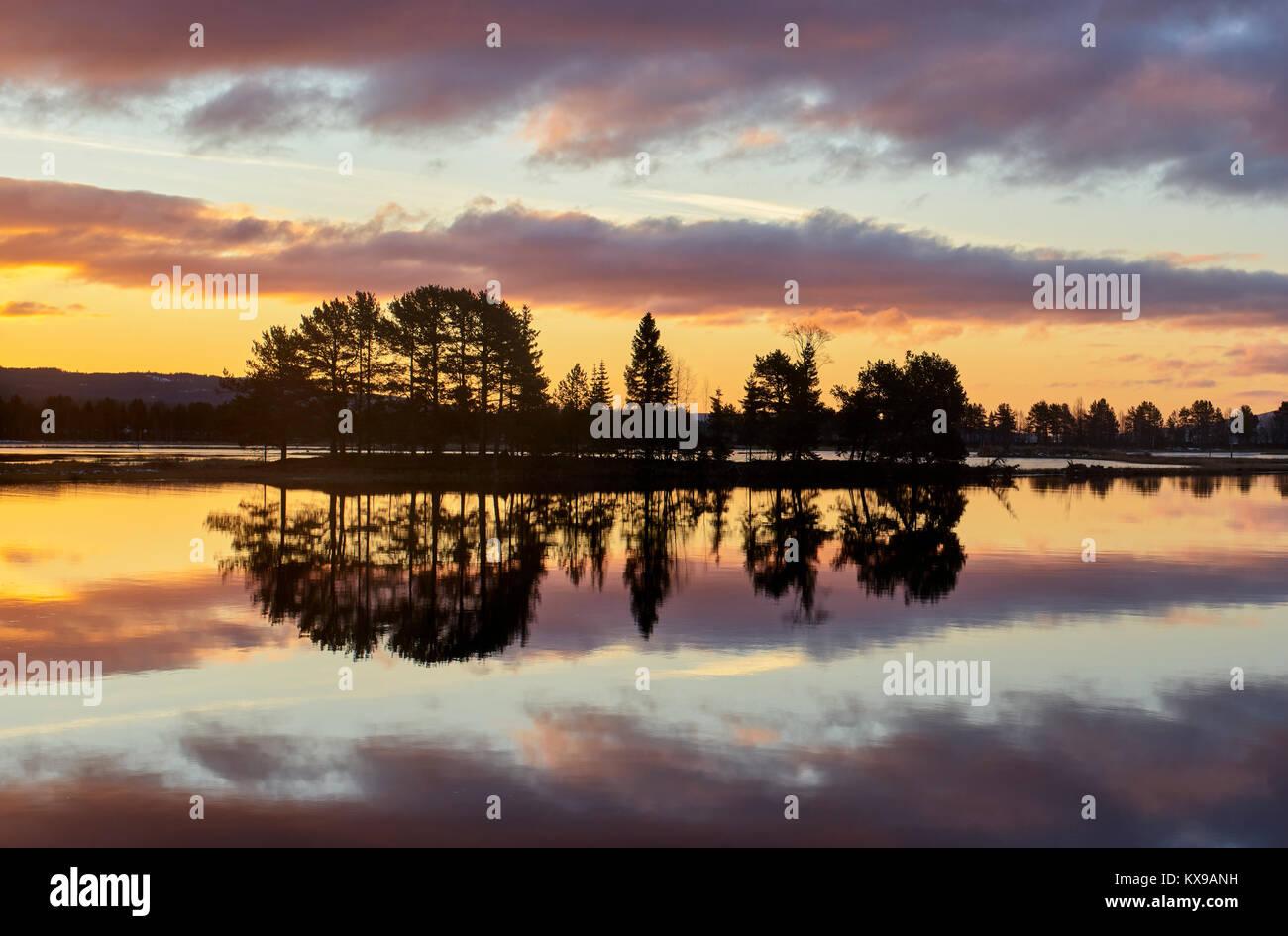 Amanecer sobre Osensjoen de Sandvik, Hedmark, Noruega. Imagen espejo reflejo Foto de stock