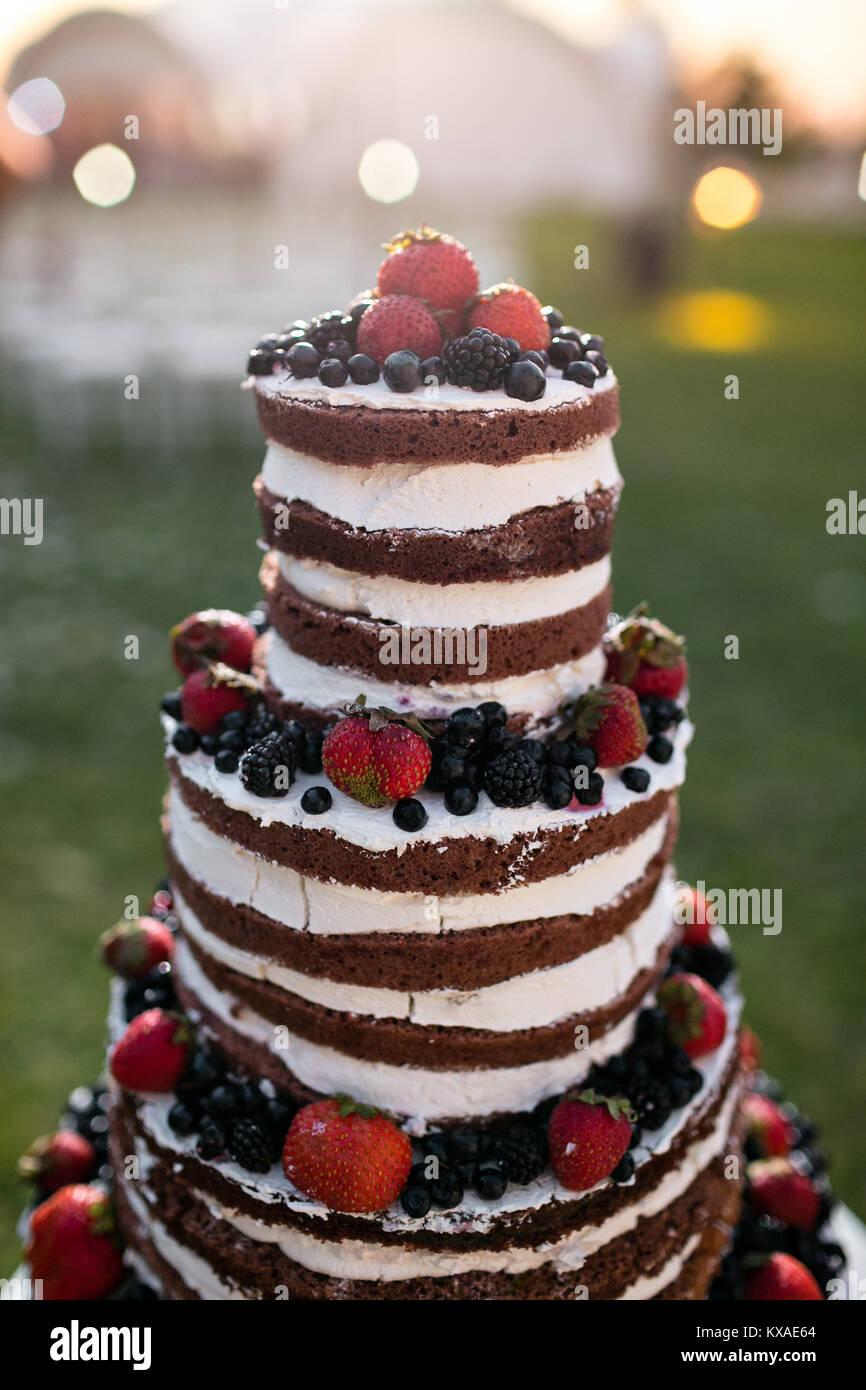 Pastel de boda de varios niveles redondo con la esponja, crema, mermelada y bayas en una base circular. Arándanos Imagen De Stock