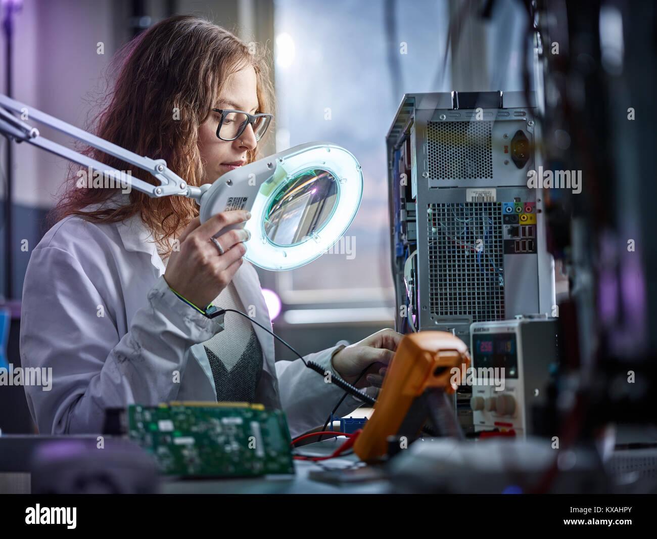 Técnico con bata blanca de laboratorio con un dispositivo de medición en un laboratorio de electrónica, Imagen De Stock