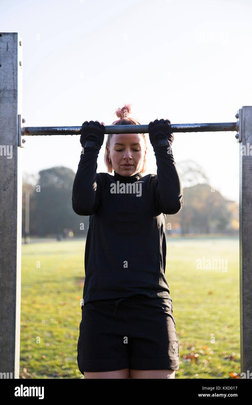 Mujer haciendo chin-ups en equipo para hacer ejercicio en park Imagen De Stock