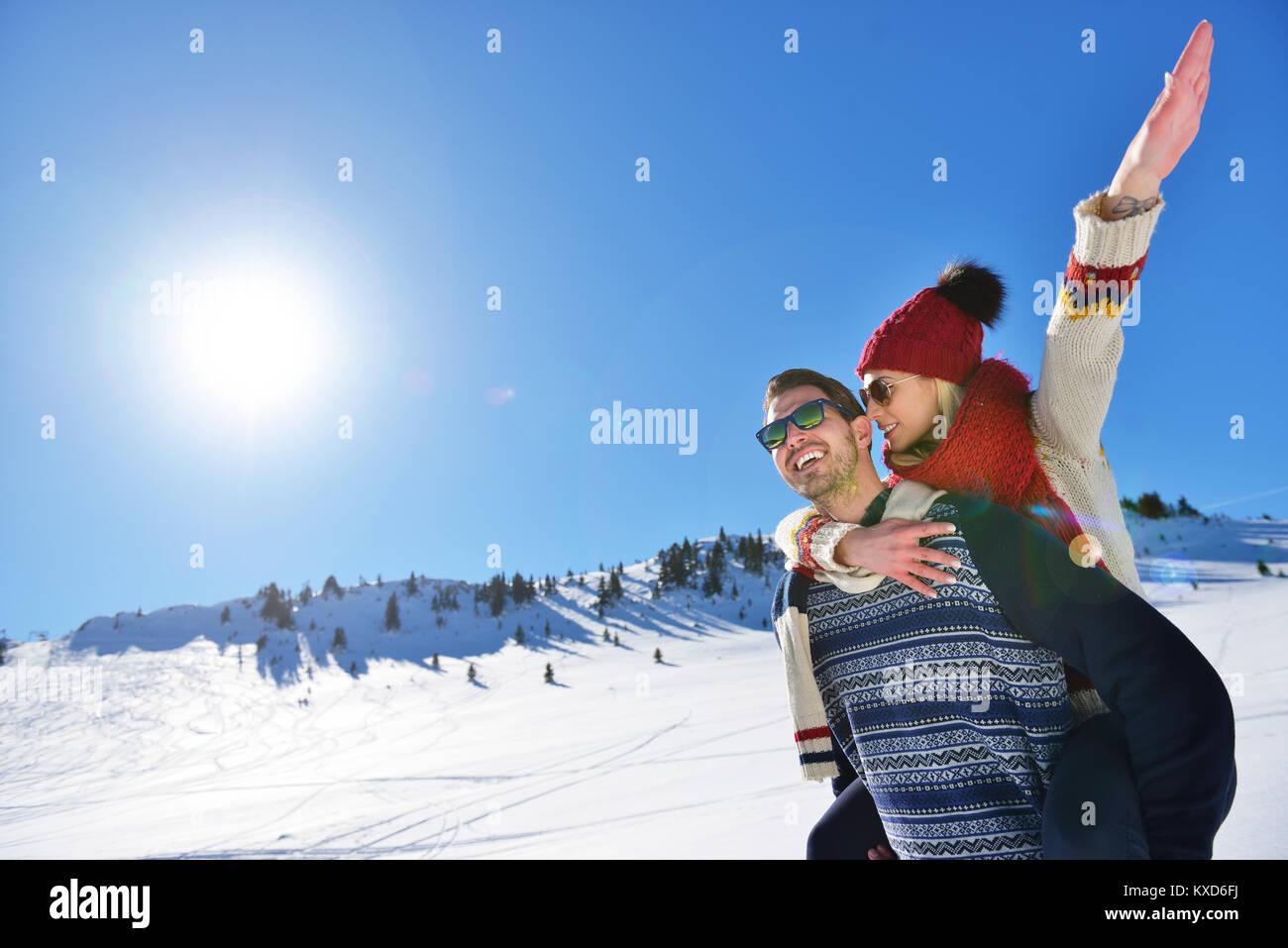 Pareja joven divirtiéndose en la nieve. Hombre feliz en la montaña dando piggyback paseo a su novia sonriente. Imagen De Stock