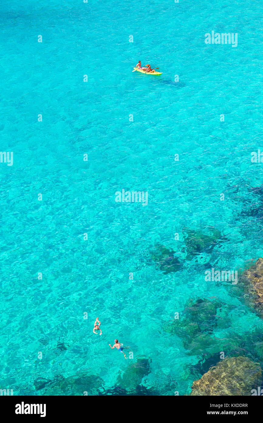 La gente de piragüismo y natación en Cala Mitjana, Menorca, Islas Baleares, España Foto de stock
