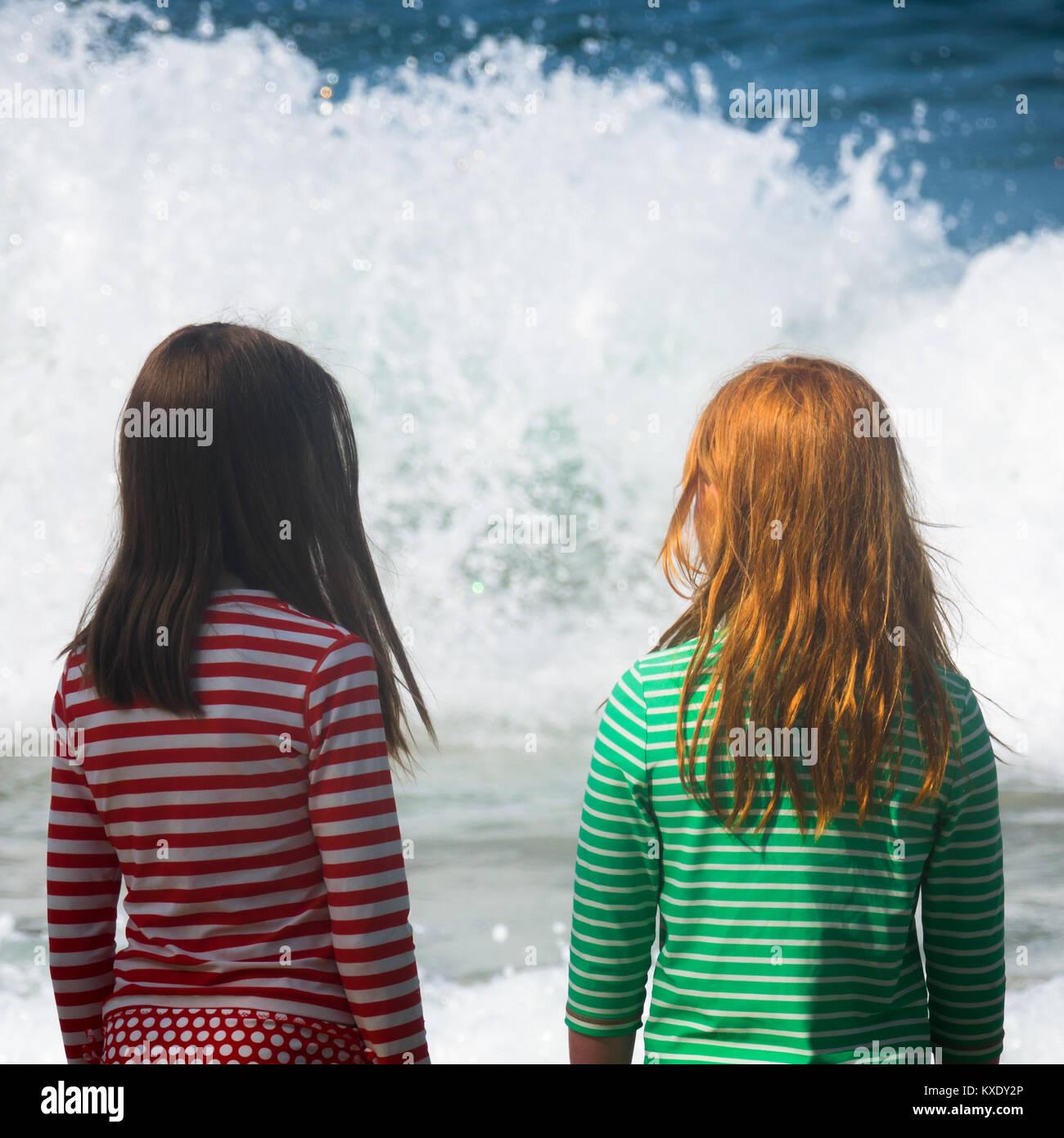 Dos niñas mirar el mar con olas grandes Imagen De Stock