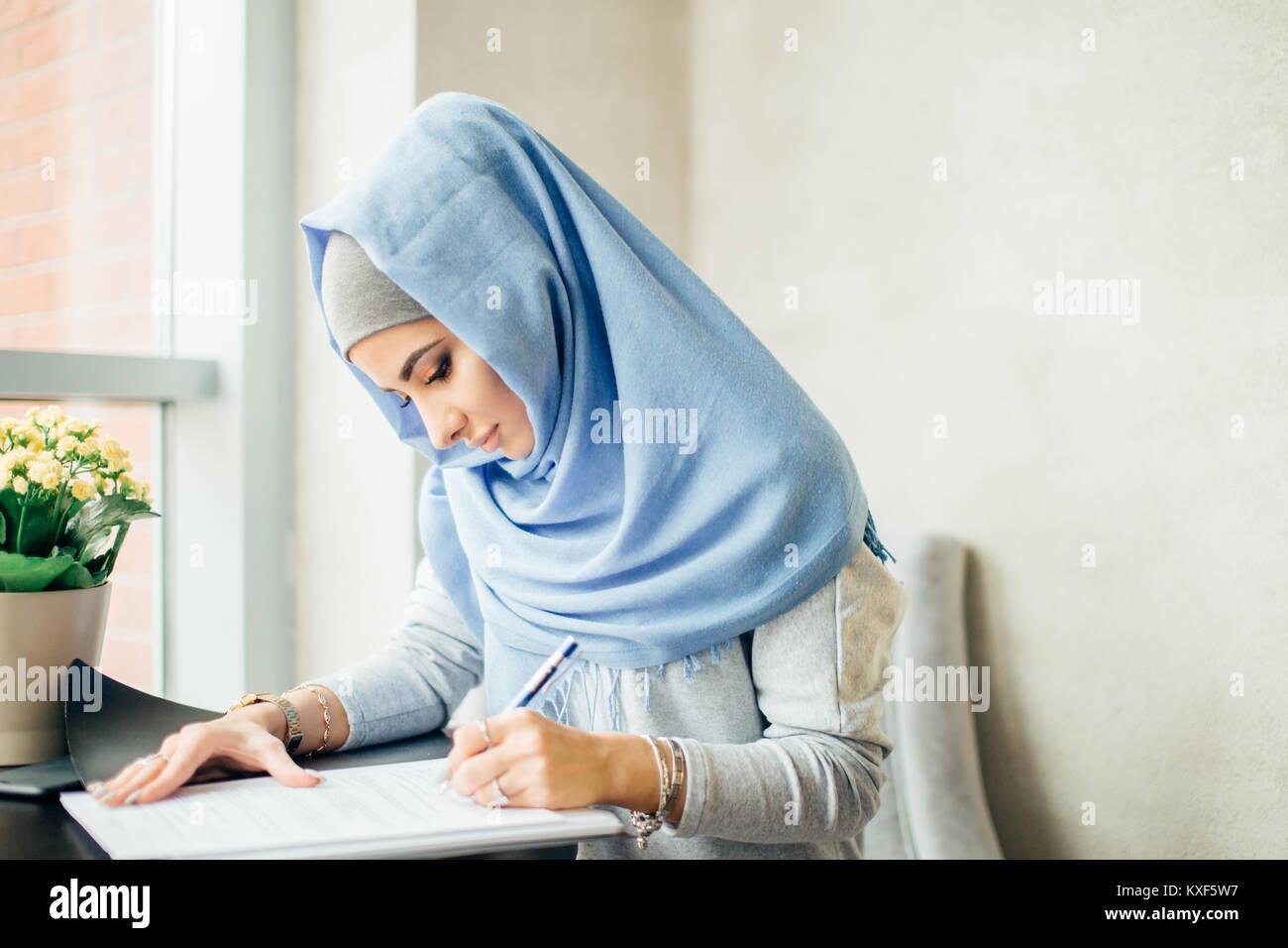 Hermosa mujer musulmana para trabajar con documentos de negocios, concepto de estilo de vida. Imagen De Stock