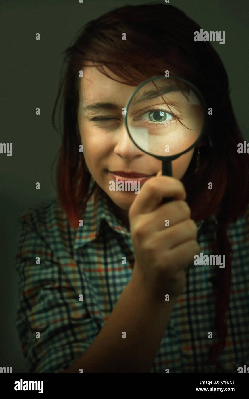 Gracioso spy joven mirando a través de una lupa Imagen De Stock