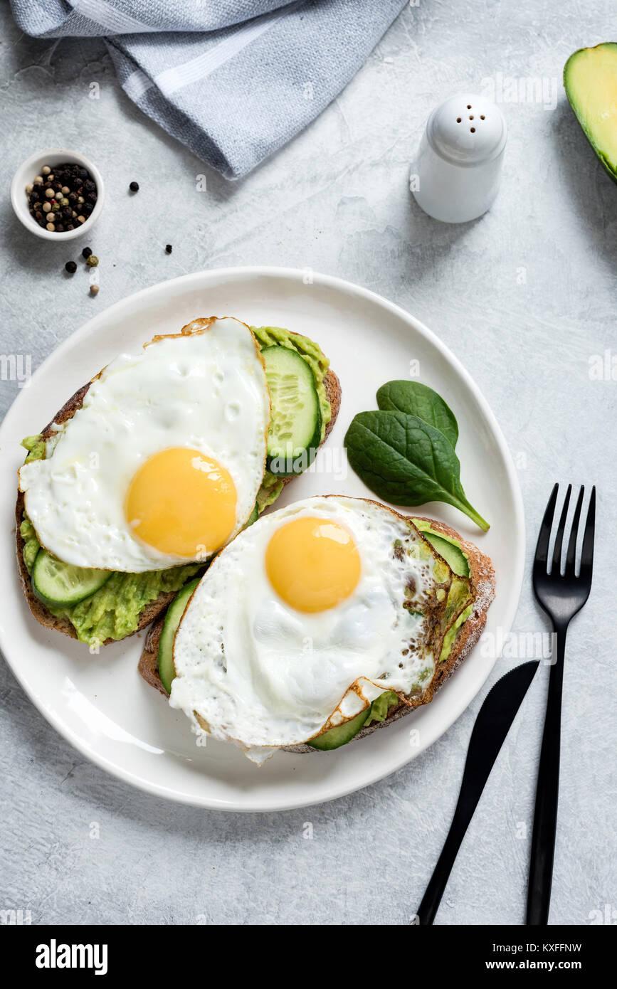 Huevo frito, aguacate y pepino sobre pan tostado de granos enteros . La alimentación sana, el concepto de comida Imagen De Stock
