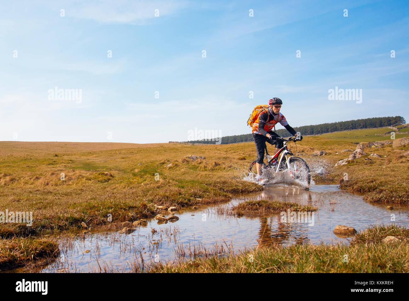 Ciclista de montaña salpicando a través de un Ford en Crosby Ravensworth cayó en Yorkshire Dales Imagen De Stock