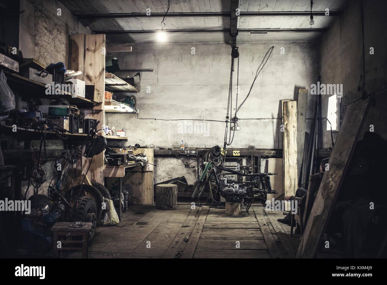 Mechanic sentado en un sillón viendo desmantelado Vintage Motorcycle en taller Foto de stock