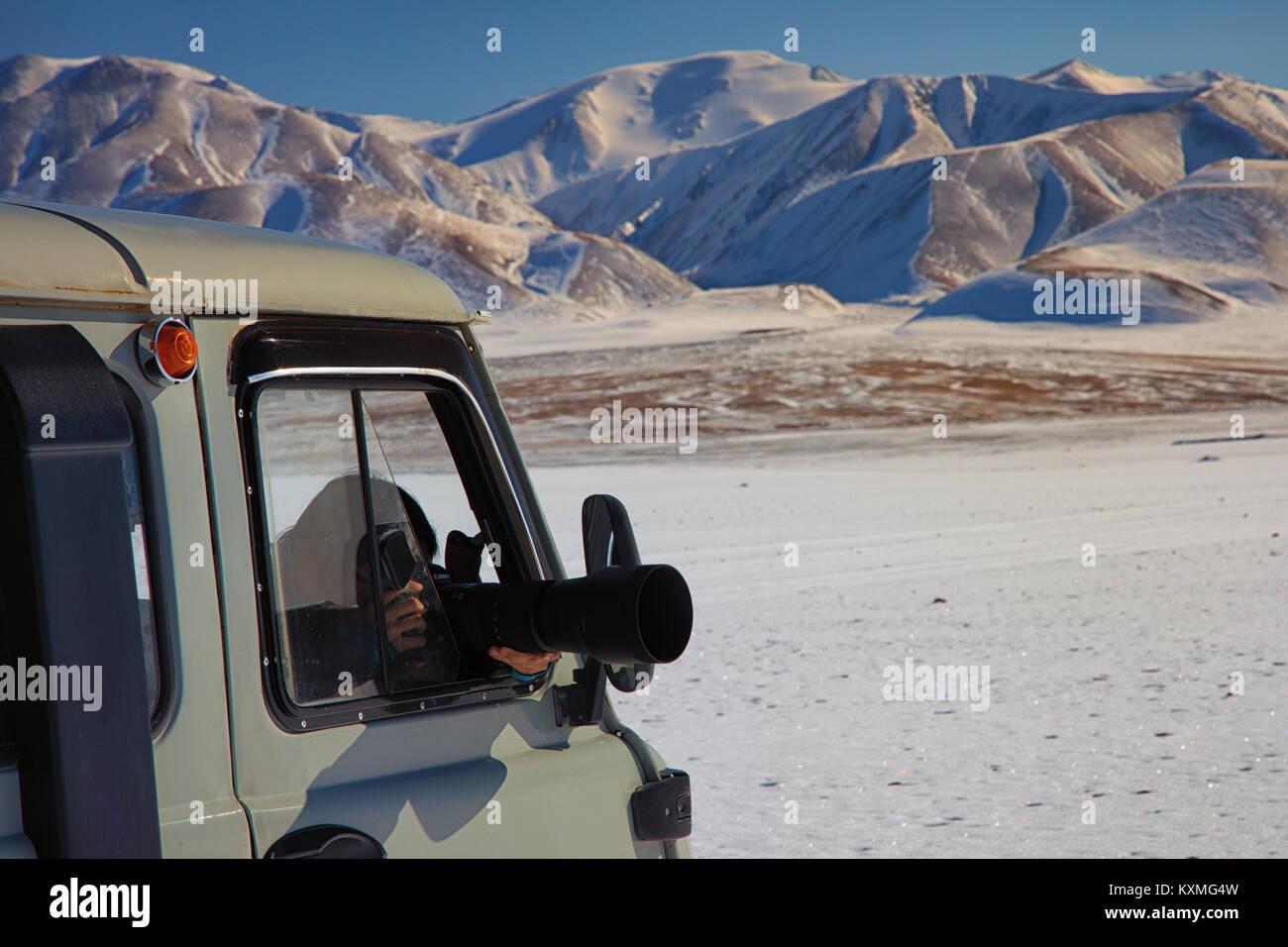 Chica tomando fotografías van ruso UAZ 452 camper dslr lengs zoom sigma 150-600mm invierno nieve Mongolia nevados Imagen De Stock