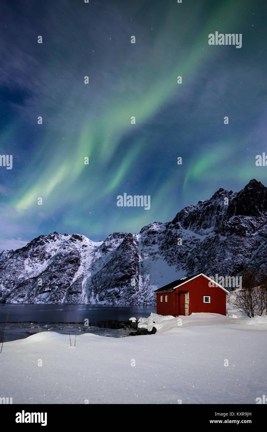 , Svolvaer Lofoten, Aurora Borealis sobre un lago congelado y rojo rorbu, Noruega. Foto de stock