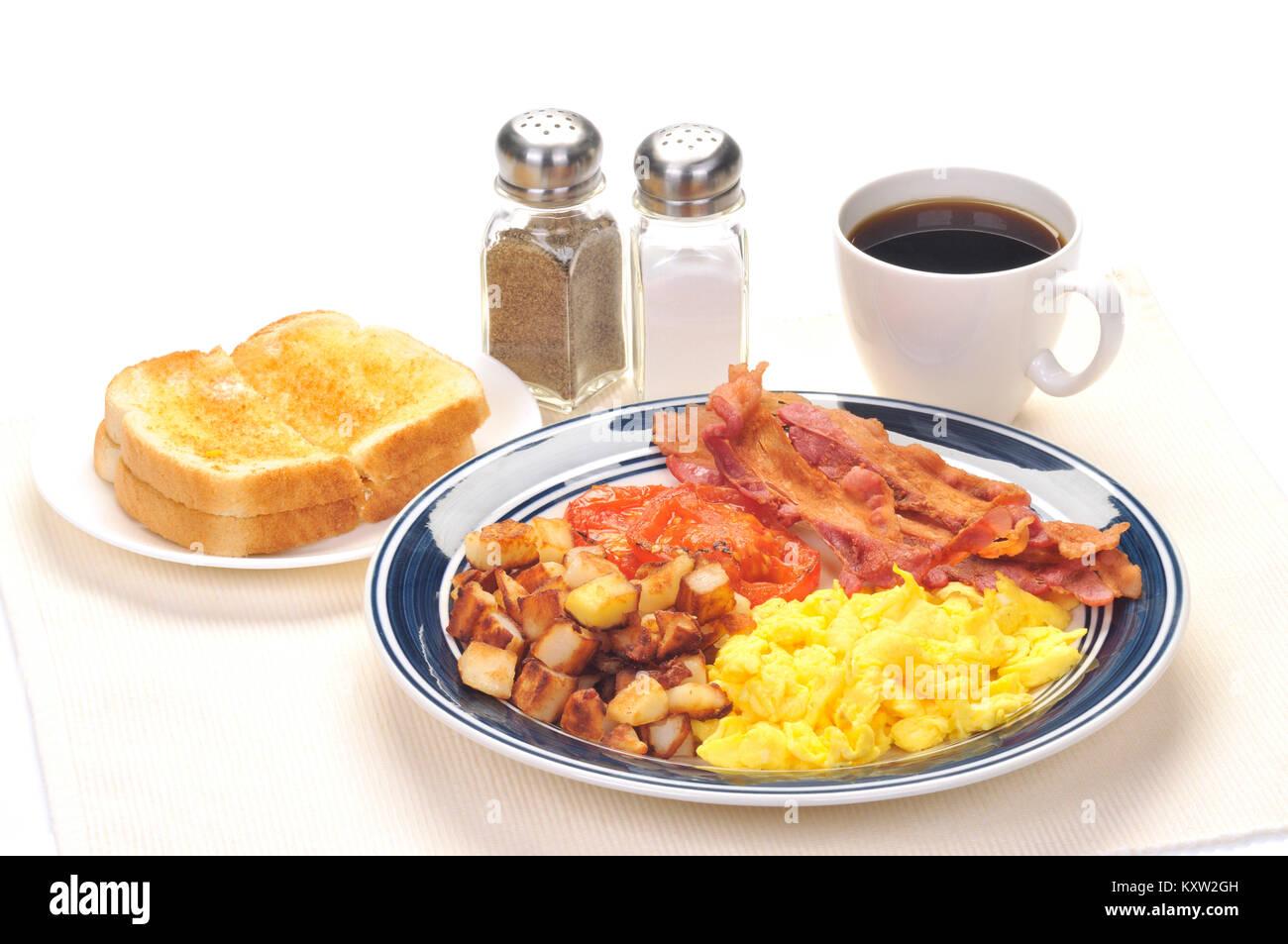 Placa azul desayuno especial con huevos revueltos, papas ralladas, tiras de tocino, tomates asados, pan blanco tostado Foto de stock