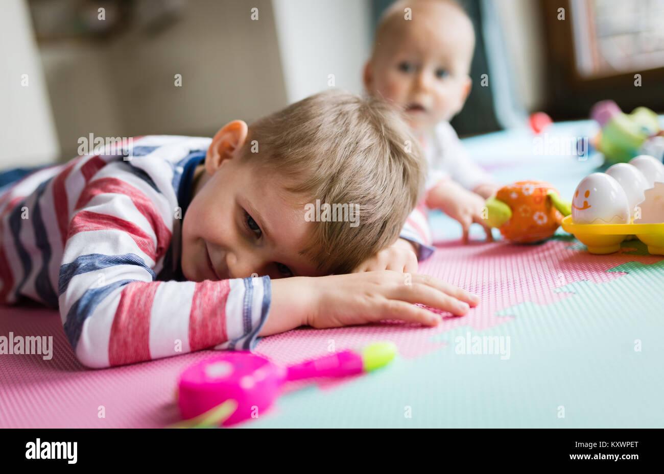 Cute little niños jugando mientras está sentado sobre una alfombra Imagen De Stock
