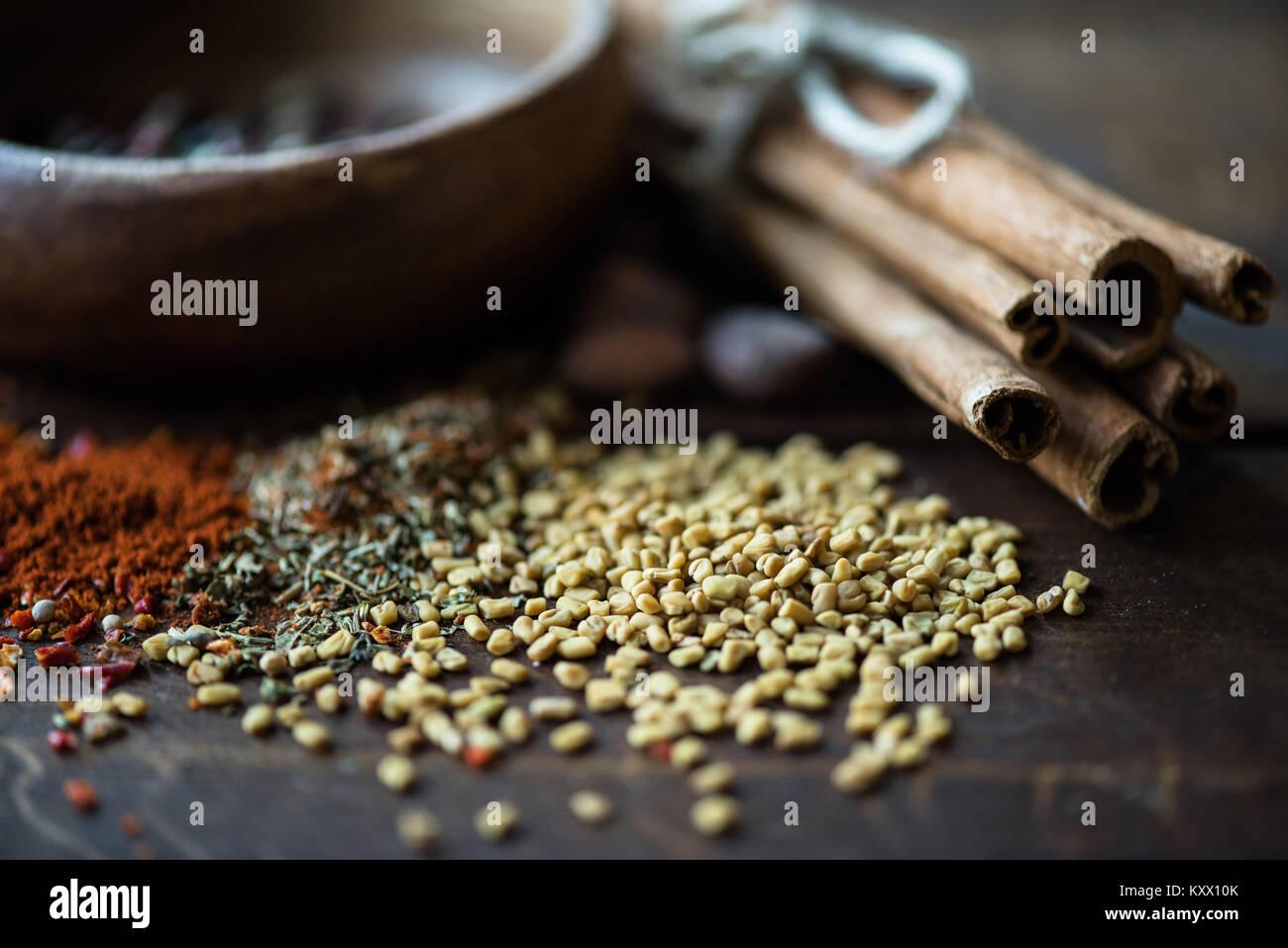 Cerrar dispersas de las semillas de sésamo y hierbas con canela en tablero de madera Foto de stock