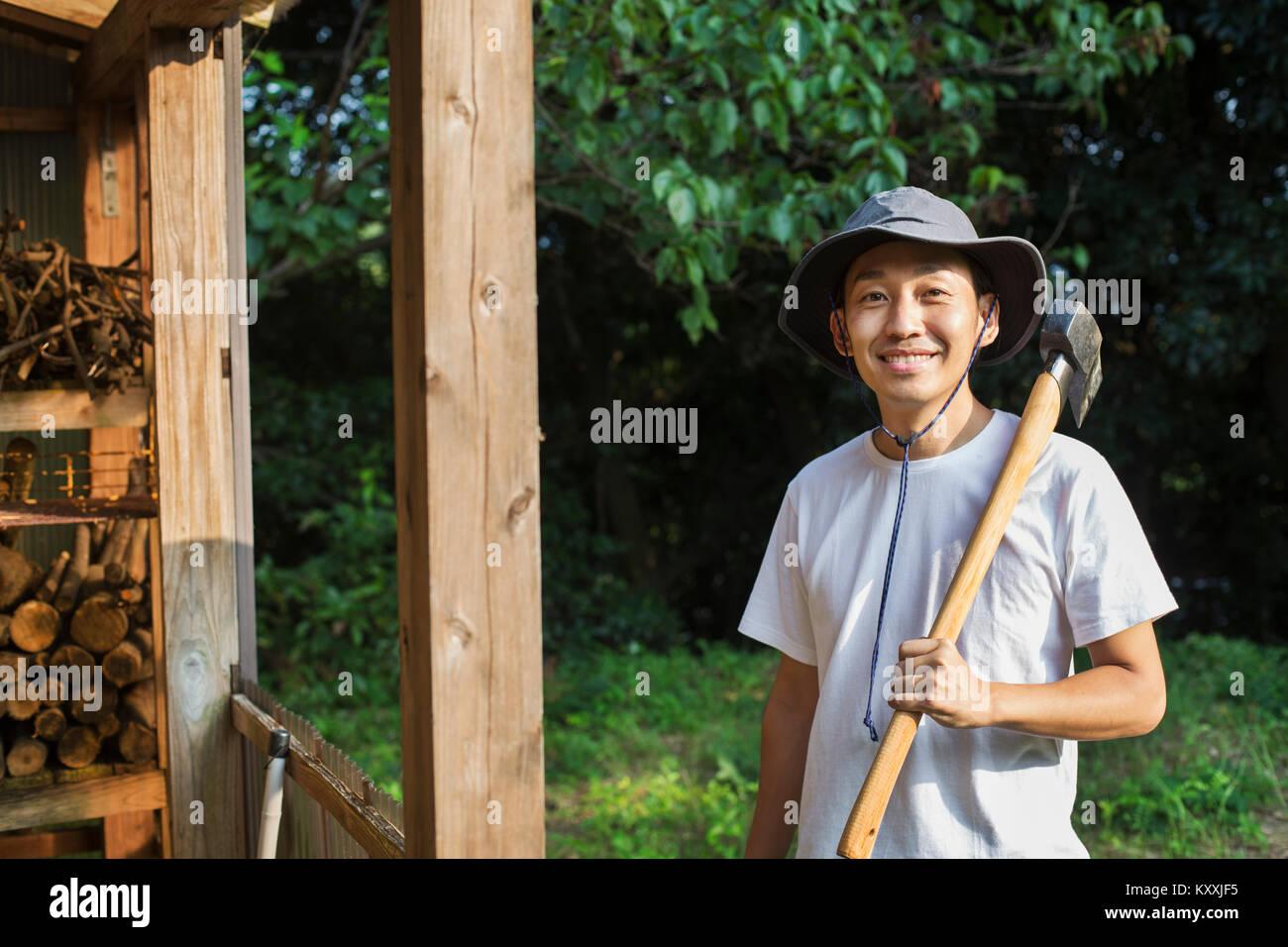Sonriente hombre vestido con sombrero de pie en el jardín b32d6446b22