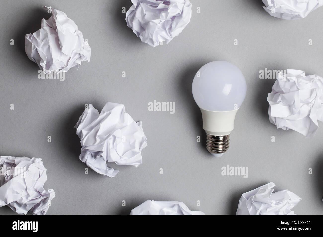 La inspiración y la imaginación concepto. bombilla blanca con documentos de papel arrugado Imagen De Stock