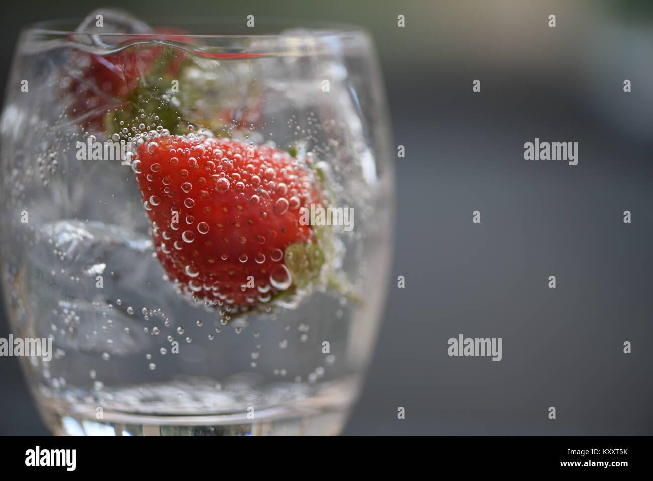 Comida y bebida refrescante cerca de macro fotografía imagen de fruto rojo fresa en una copa de espumoso de cubos Foto de stock