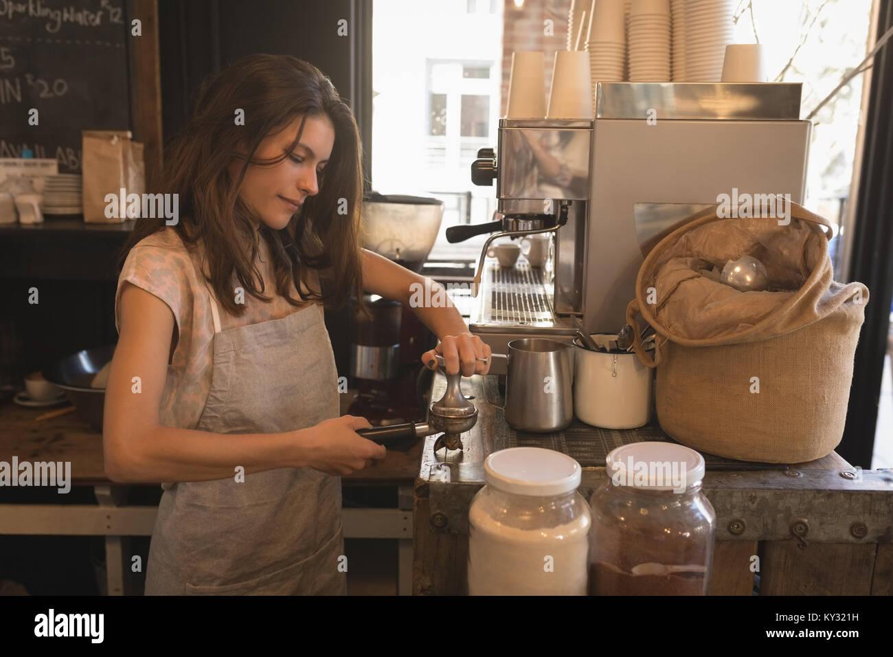 Barista utilizando una prensa antisabotaje para café molido en un portafilter Imagen De Stock