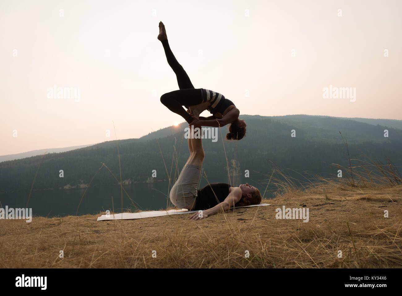 Pareja deportiva practicando yoga acro en un exuberante terreno verde Imagen De Stock
