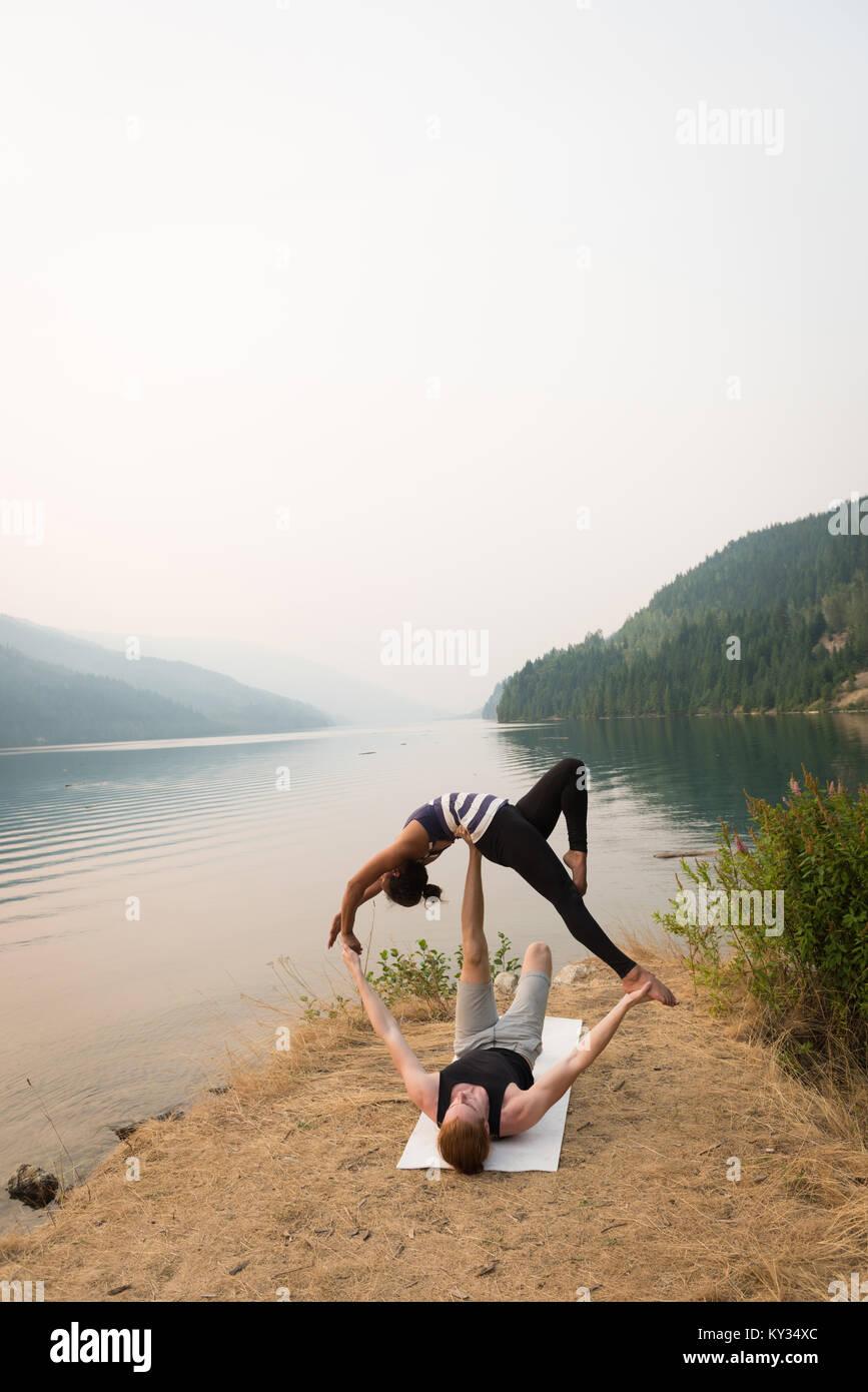 Colocar par practicar yoga acro en un exuberante terreno verde Imagen De Stock