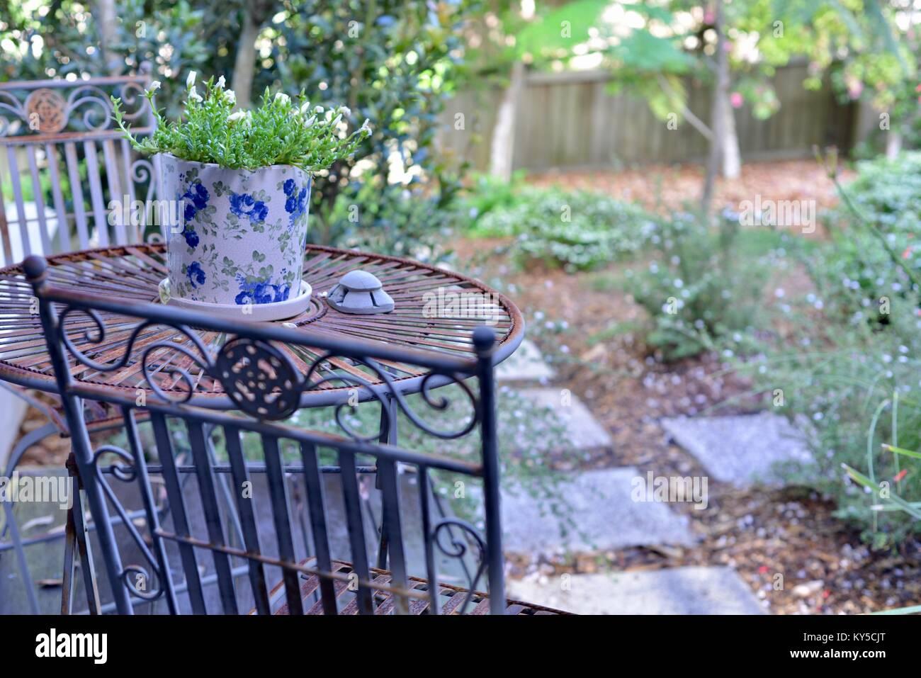 Muebles de hierro forjado, mesa y sillas, en un patio con vistas a ...