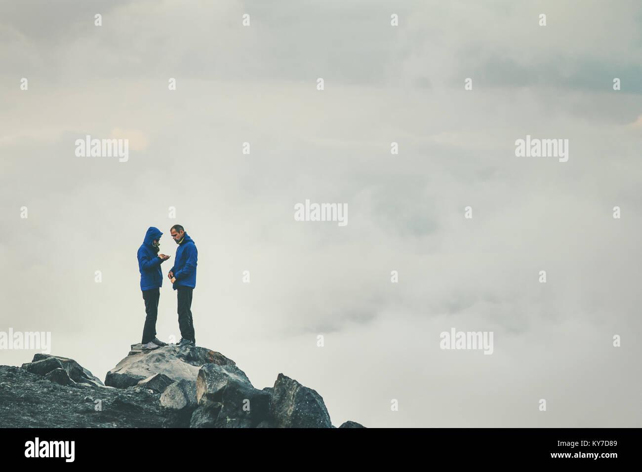 Par viajeros en amor de pie sobre el acantilado juntos disfrutando nublado brumosas montañas paisaje Lifestyle Imagen De Stock