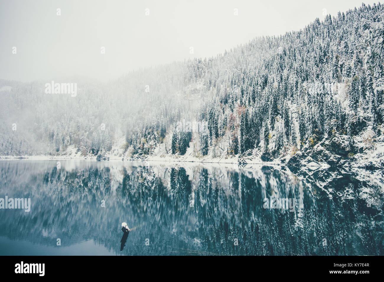 Lago de invierno cubierto de nieve y bosques de coníferas paisaje brumoso viaje serena vista panorámica Imagen De Stock