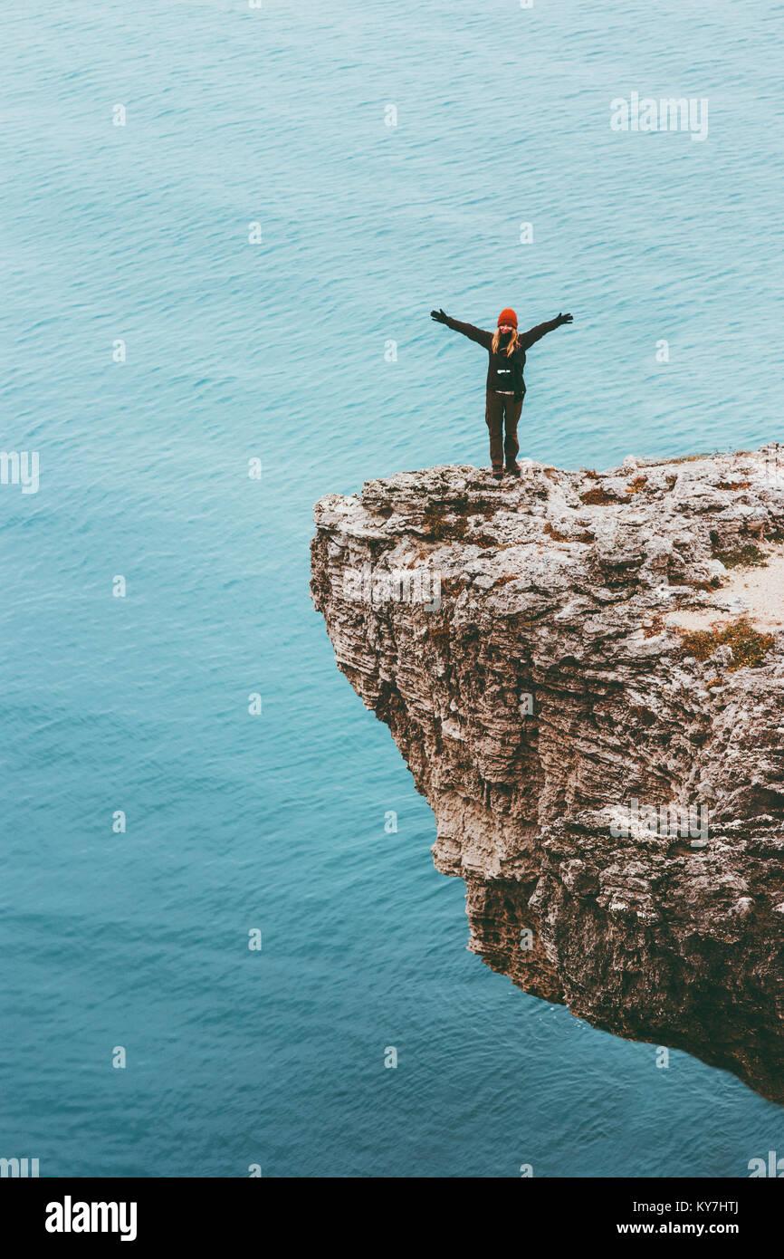 Viajero feliz sobre un acantilado sobre el mar manos levantadas Lifestyle Viajes éxito motivación concepto Imagen De Stock