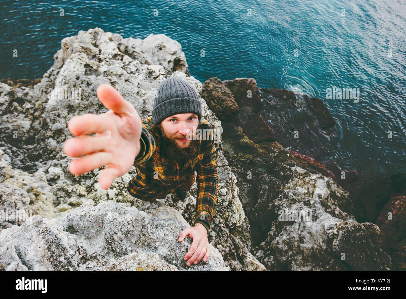 Hombre ayudar dando la mano de viaje vacaciones en concepto de estilo de vida al aire libre en el mar Imagen De Stock
