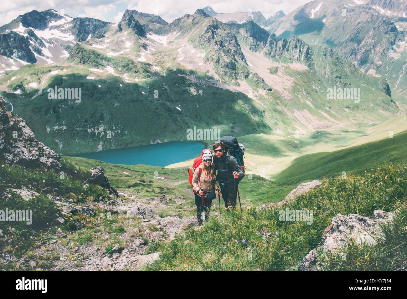 Par los viajeros al hombre y a la mujer la escalada en las montañas de amor y de emociones felices viajes concepto Foto de stock