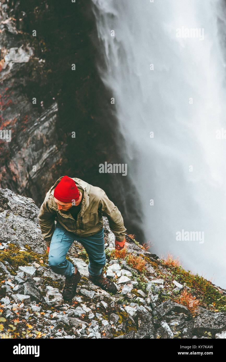 Hombre senderismo cascada montañas Outdoor Lifestyle Viajes Vacaciones de aventura en concepto de supervivencia Imagen De Stock