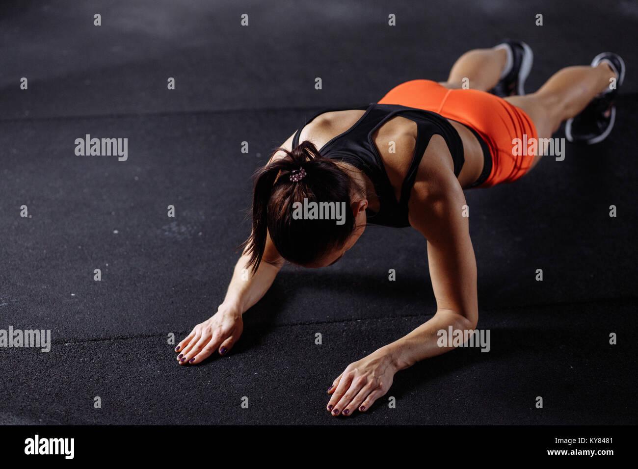 Bella mujer en ropa deportiva haciendo plank mientras trainnig at Cross fit gimnasio Imagen De Stock