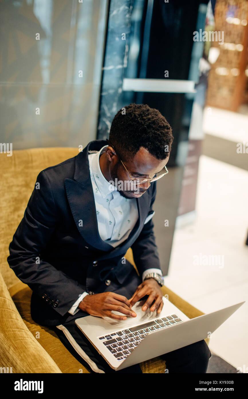Vestidos de traje empleado trabajando en línea en portátil Imagen De Stock