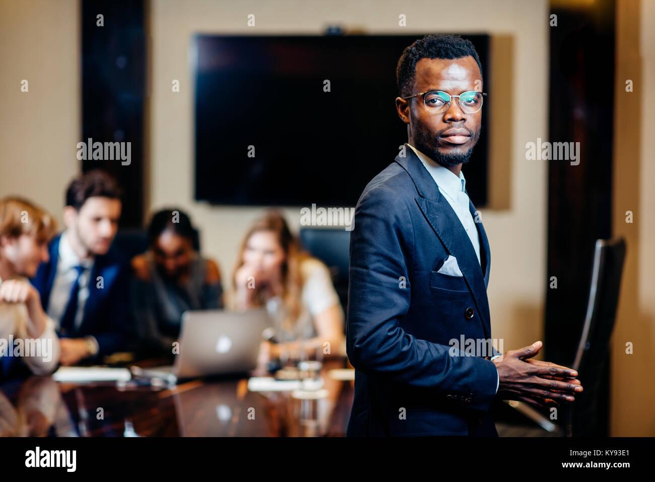 Empresario africano mirando a la cámara con un grupo de empresarios sobre antecedentes Foto de stock