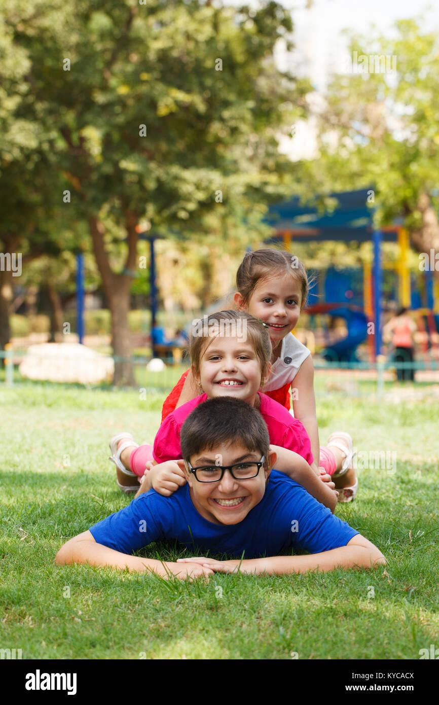 Los niños felices de tres jugar piggy back, mirando a la cámara. Imagen De Stock