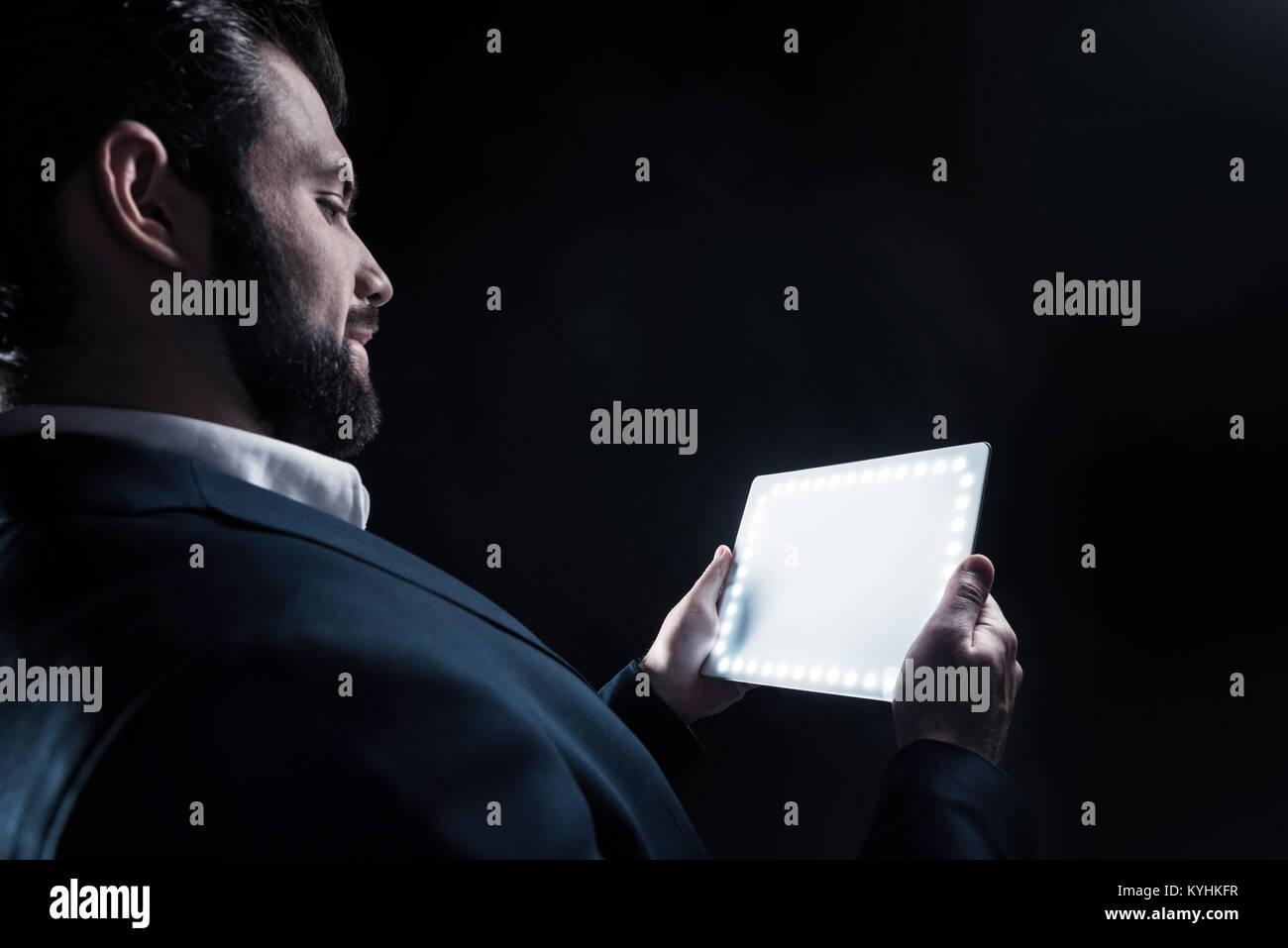 Alegre empresario positivo mirando su tablet Foto de stock