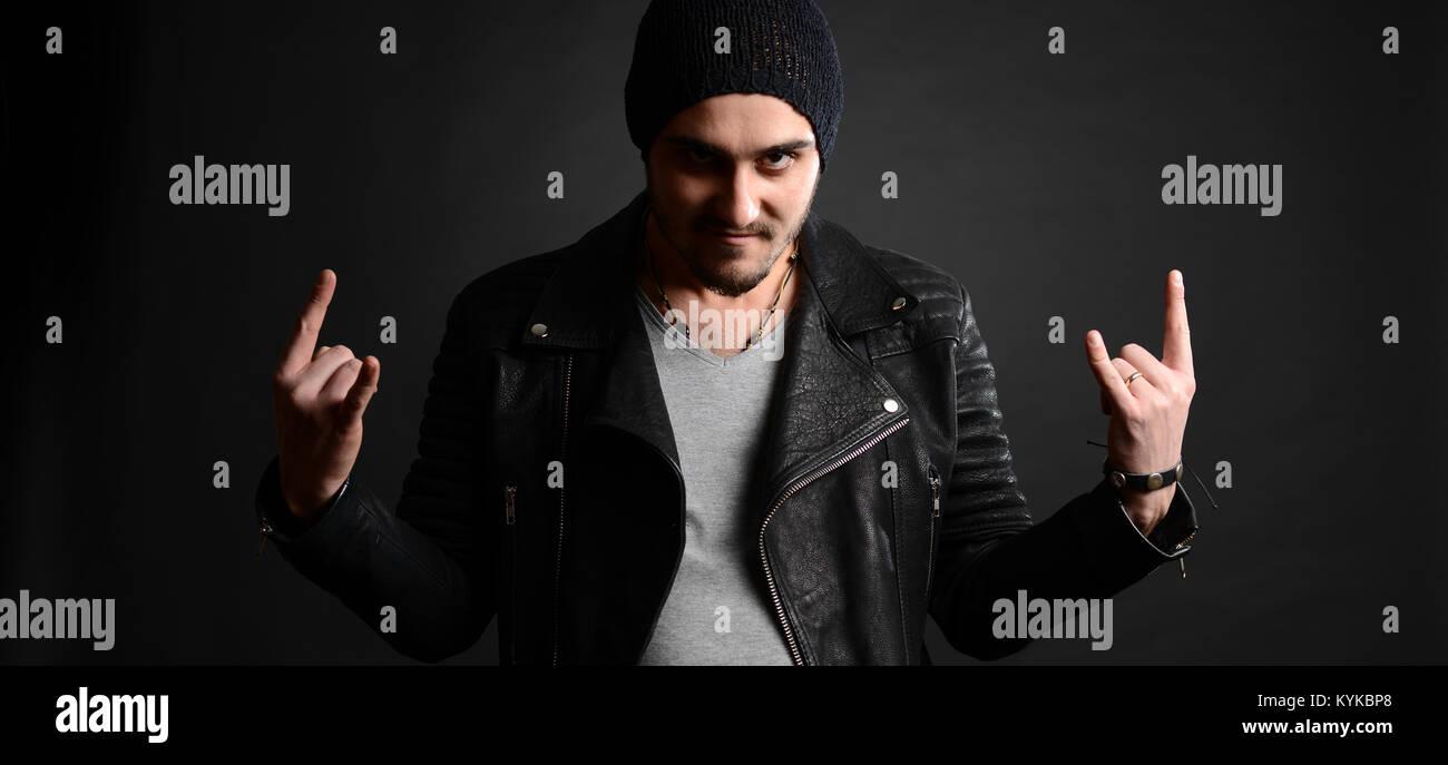 El cantante de rock retrato, con chaqueta de cuero y una actitud fresca sobre fondo negro, foto de estudio Imagen De Stock