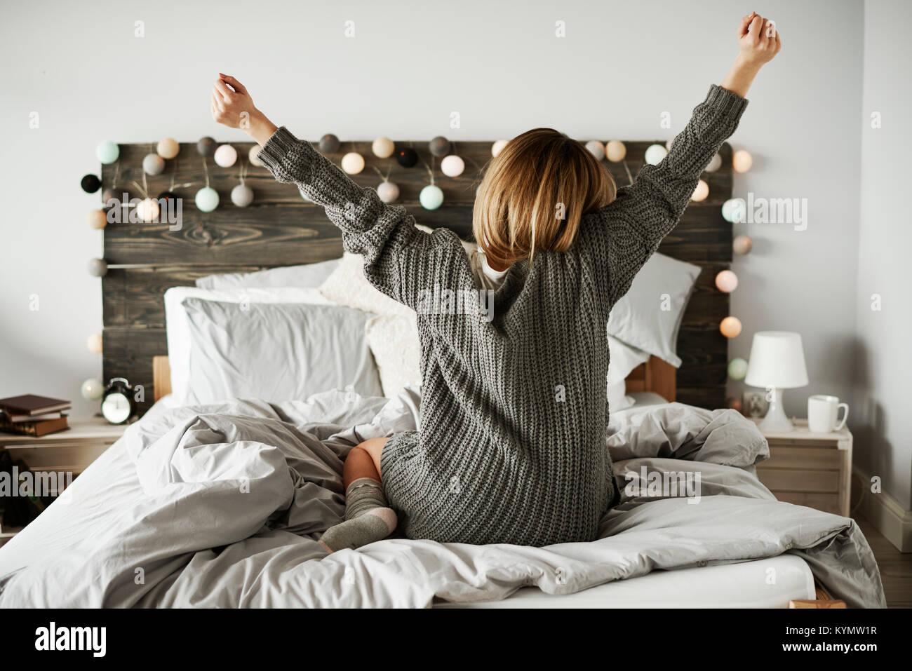 Vista trasera de la mujer en su cama de estiramiento Imagen De Stock