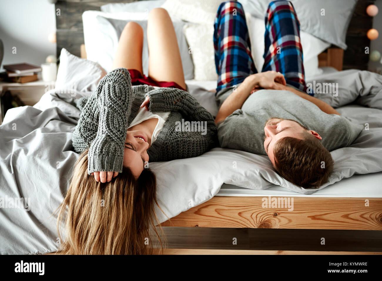 Vista trasera de la alegre pareja acostada en la cama Imagen De Stock