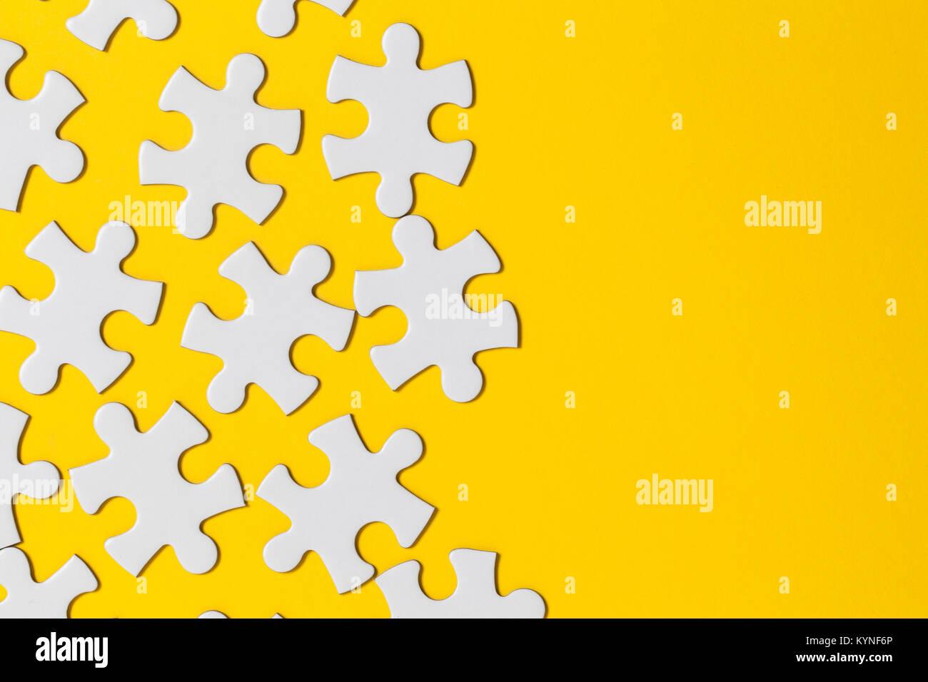 Las piezas de un rompecabezas blanco sobre un fondo amarillo. Concepto de Solución empresarial Imagen De Stock