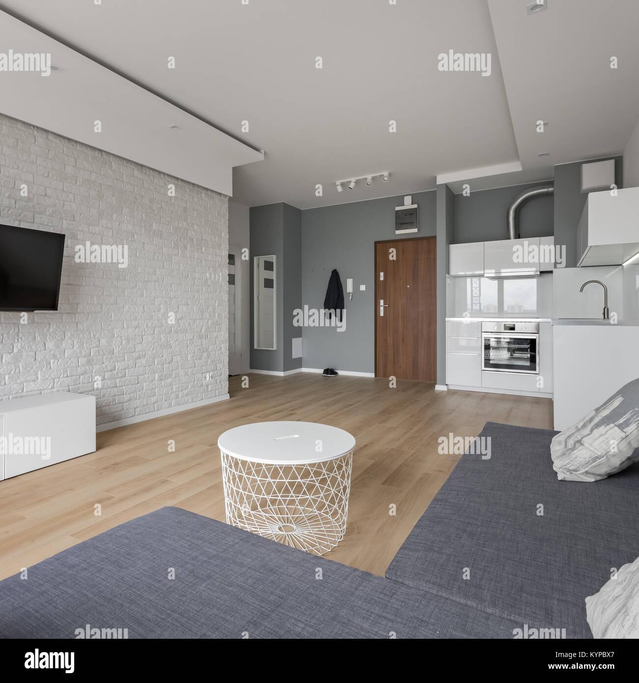 Piso moderno con sala de TV, sofá, mesa de café y una pequeña cocina ...