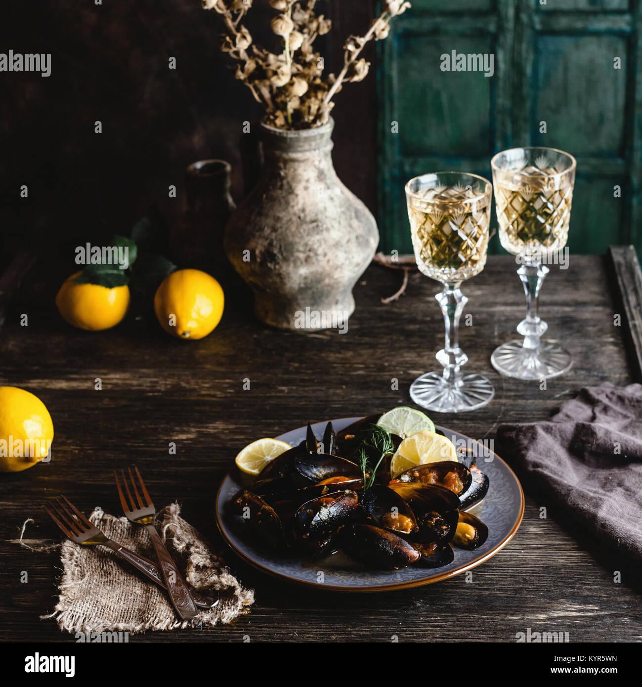 Mejillones cocidos con conchas sirvió en la placa con dos copas de vino blanco sobre la mesa de madera Foto de stock
