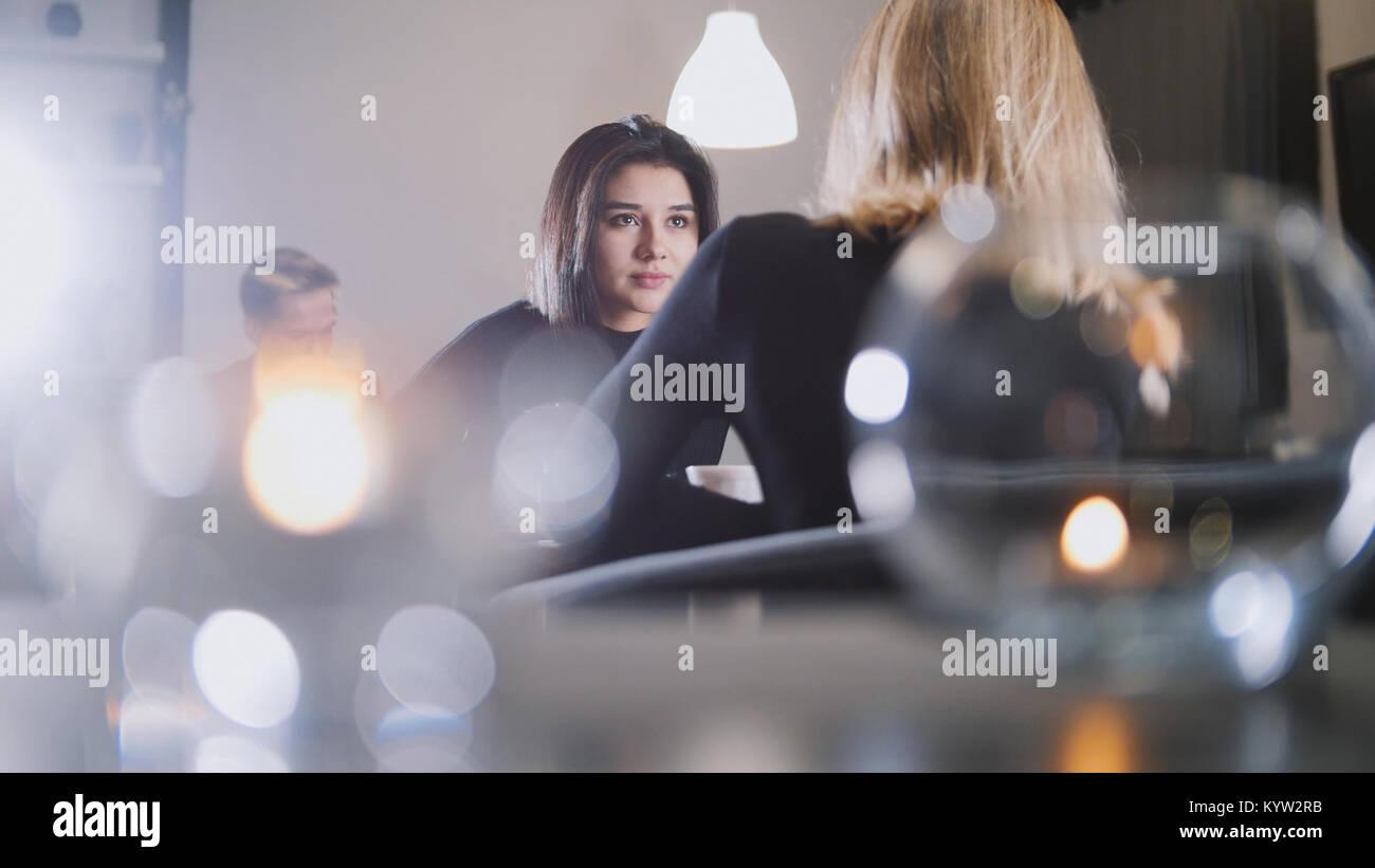 Bastante joven con cabello negro bebiendo café y hablando con mi novia en la cafetería Imagen De Stock