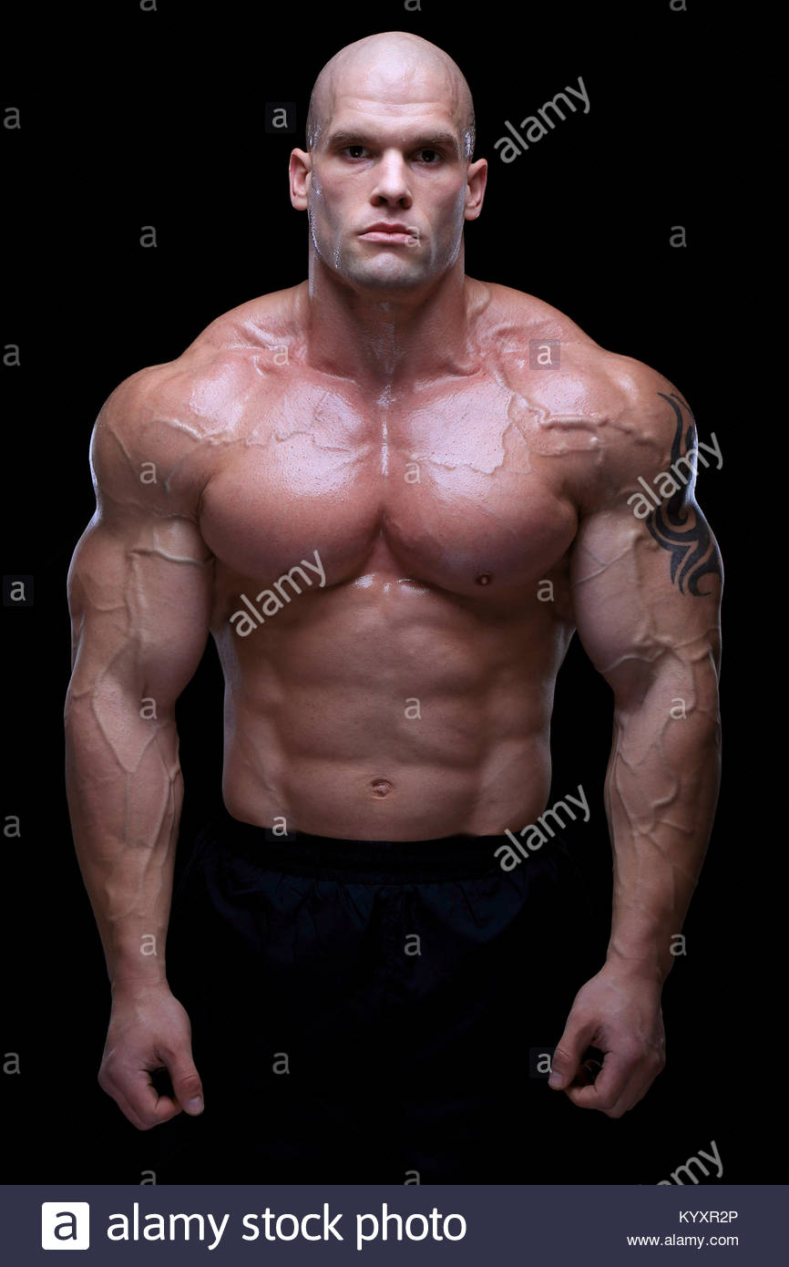 Guapo macho musculoso posando delante de fondo negro Imagen De Stock