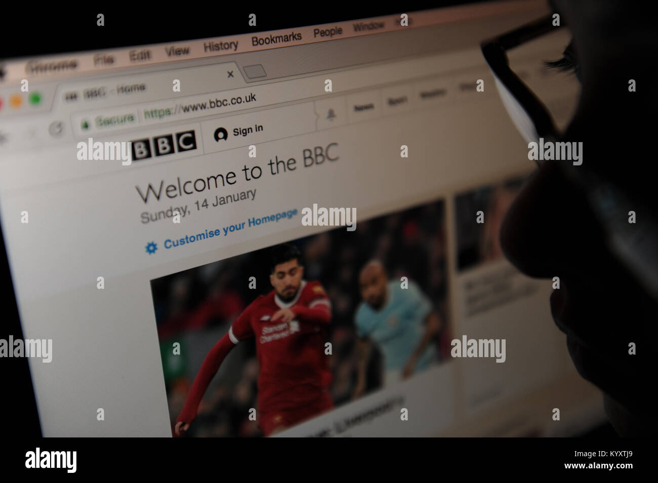 Una mujer mira a la BBC News homepage Imagen De Stock