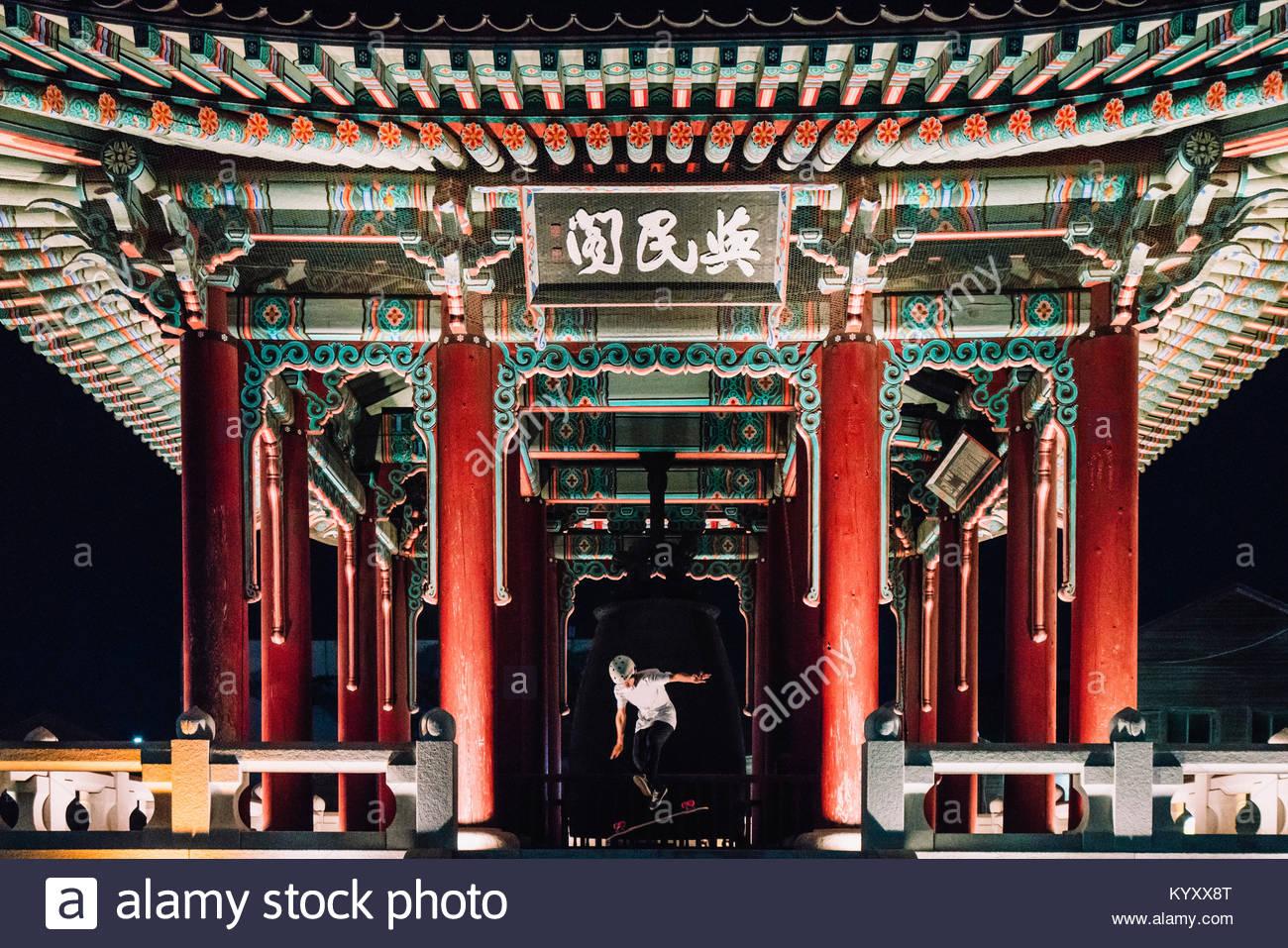 Hombre saltando en monopatín en pabellón de la fortaleza de Hwaseong Imagen De Stock
