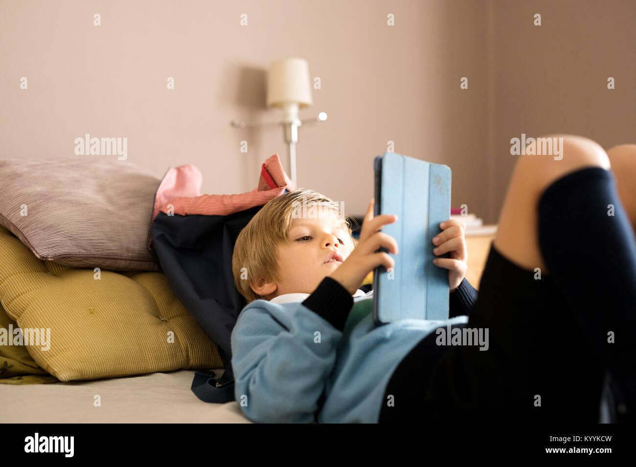 Boy utilizando tablet digital en el dormitorio en el dormitorio Imagen De Stock