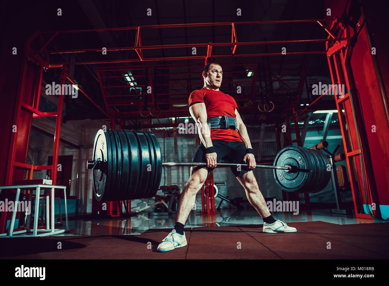 Hombre haciendo ejercicios musculares deadlift barbell en un moderno centro de fitness. El entrenamiento funcional. Imagen De Stock